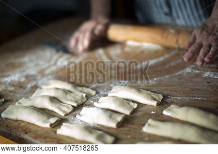 Typical Asturian Christmas Dessert. Aged Woman's Hands With A Rolling Pin Preparing At Home Casadiel