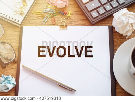 On A Wooden Table There Is An Office Sheet Of Paper With The Text Evolve. Business Workspace With Ca