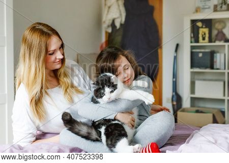 Lovely Young Mother And Cute School Kid Girl Cuddling Together With Cat In Bed In Morning. Happy Fam