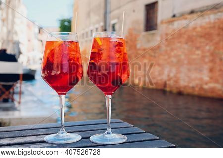 Two glasses of Spritz Veneziano cocktail served near the Venetian canal.  Popular italian summer ape
