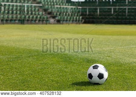 Classic Soccer Ball On Stadium Field. Row Of Seats In The Stadium In The Background. Football Arena