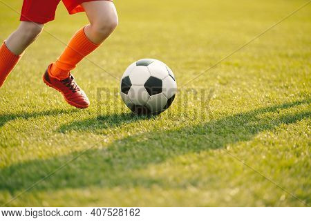 Closeup Of Soccer Player Legs In Run. Young Player Running Football Ball On Grass Field. Player In S