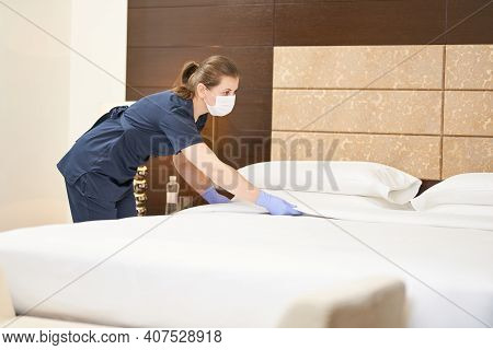 Chambermaid In Uniform Is Busy While Cleaning The Bedroom