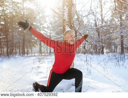 Fitness Suspension Training Concept. Athletic Senior Man Working Out With Sports Equipment On Snowy