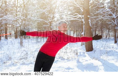 Outdoor Functional Strength Training Concept. Senior Athletic Man Stretching His Arm Muscles With Re