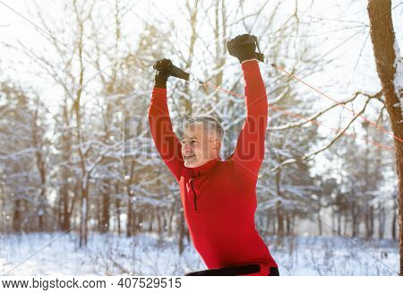 Outdoor Functional Training Concept. Healthy Mature Man Using Suspension Straps To Exercise Upper Bo
