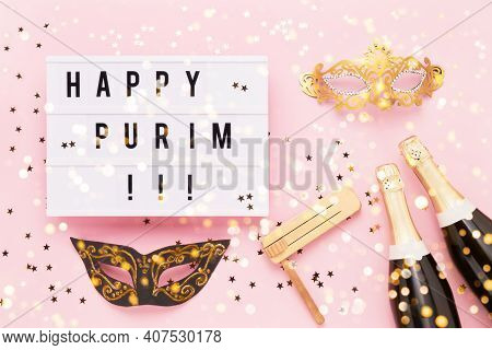 Flat Lay Of Purim Carnival Celebration Concept. Happy Purim Written In Light Box, Champagne Bottles,