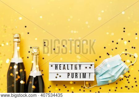 Healthy Purim Written In Lightbox And Two Champagne Bottles, And Medical Mask On A Yellow Background