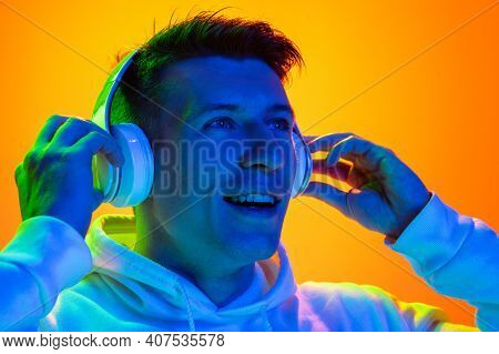 Delighted. Caucasian Mans Portrait Isolated On Yellow Studio Background In Mixed Neon Light. Listeni