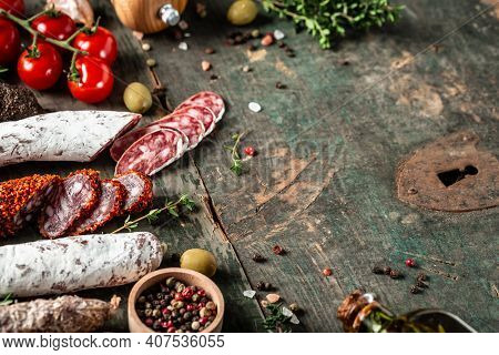 Variety Of Dry Cured Chorizo, Fuet And Other Sausages Cut In Slices With Herbs On Wooden Background.