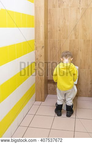 Child Boy Kid Pissing In Toilet Bowl In Children Toilet With Yellow Tiles. Hygiene Concept In Public