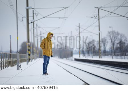 Snowy Railroad Station During Frosty Day. Man Standing On Platform And Waiting For Delayed Train.