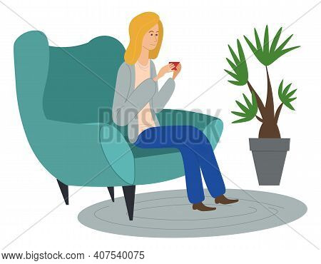 Blond Girl Sitting In Green Cozy Chair And Holding Red Cup. On Floor There Is Gray Oval Rug, Home Pa