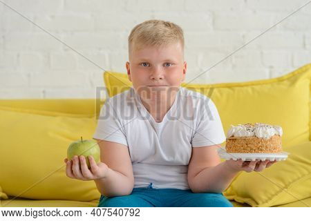 Boy Holding Apple And Cake. Portrait Of A Fat Child With Health And Junk Foods