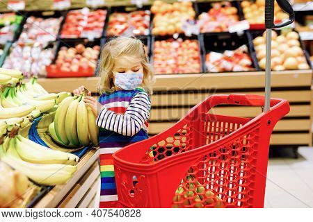 Cute Todler Girl With Medical Mask Pushing Shopping Cart In Supermarket. Little Child Buying Fruits.