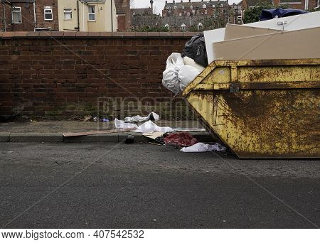An Overflowing Skip With Household Waste Littering Pavements And Roads With Copy Space