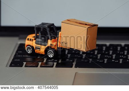 Toy Forklift With Box On A Keyboard Close-up. Logistics And Wholesale Concept