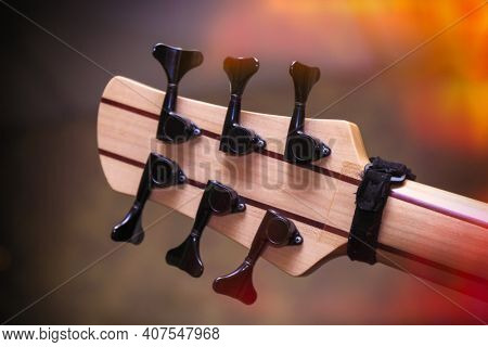 Headstock Of Six-string Bass Guitar And Neck Tuners. Rear View
