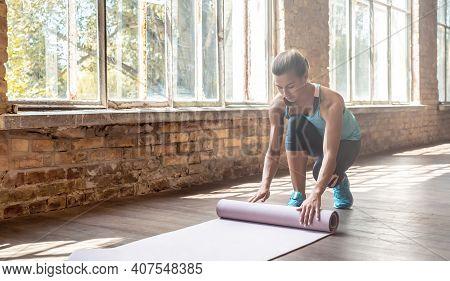 Sporty Fit Young Woman Yoga Instructor Wear Sportswear Rolling Unrolling Yoga Pilates Rubber Mat In