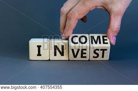 Invest Or Income Symbol. Businessman Turns Wooden Cubes And Changes The Word 'invest' To 'income'. B
