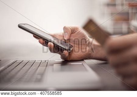 Close Up View Of Hands With Phone And Credit Card. Online Purchase From Home. Credit Card Payment.