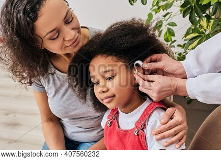 Hearing Treatment For A Child. African American Girl With Her Mother During Installation Hearing Aid