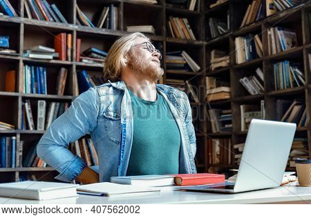 Tired Upset Young Man Teacher Student Sit At Office Home Library Desk Stretching Feel Back Pain Ache