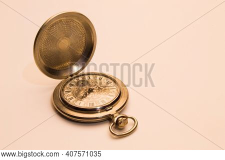 Old Pocket Watch Inlaid With An Open Cover On A Light Background