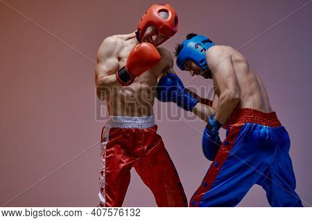 Sparring Of Two Fighting Males In Helmets And Boxing Gloves With Fit Bare Torsos During Battle, Mart