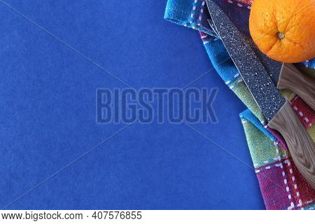 Knife, Fresh Orange, Dishcloth On A Blue Background With Space For Text. Picnic Concept. Ceramic Kni