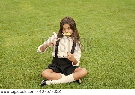 Fake Mustache. Little Child Point At Prop Mustache. Party Look Of Funny Child. Small Child Sit On Gr