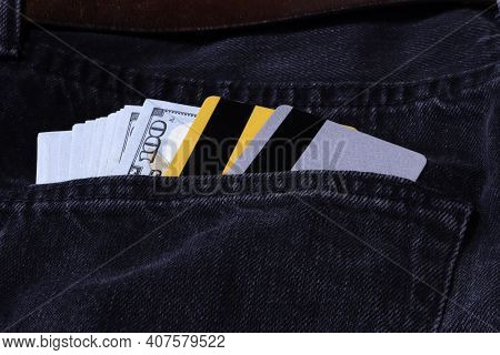 Dollar Bills And Bank Cards In Jeans Pocket Background. Dollar Banknotes In Jeans Back Pocket. Bank