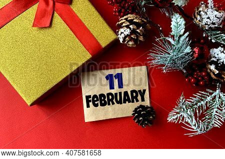 February 11 On Craft Paper. Near Fir Branches, Cones, Ribbon,gift Box On A Red Background.calendar F