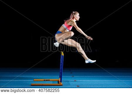 Young Sportwoman Jumps Over Hurdle On Sprint Run