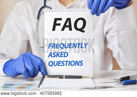 Faq Card In Hands Of Medical Doctor. Doctor's Hands In Blue Gloves Holding A Sheet Of Paper With Tex