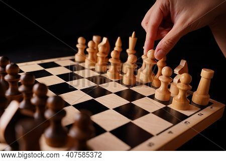 Close Up Of White And Black Wooden Chess Pieces On Board. Woman's Hand Makes First Move Of White Paw