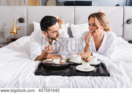Young Interracial Couple In Bathrobes Eating Breakfast Near Tray On Hotel Bed.