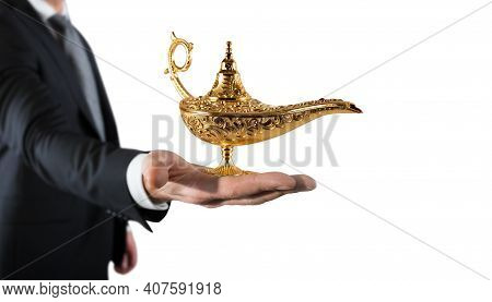 Businessman Hold A Genie Lamp Of Aladdin. Concept Of Desire And Make A Wish Come True