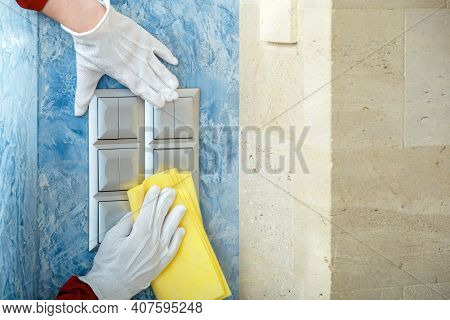 Surfaces Disinfection. Houseworker In White Gloves Clean Light Switches With Cloth On Wall By Alcoho