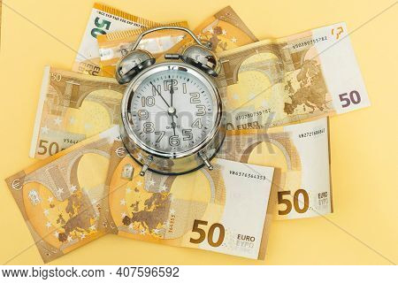 Horizontal Photo Of A Background Of Fifty Euro Banknotes And An Analogical Clock As Time Money Work