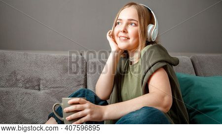 Happy Young Woman Sitting On Sofa With In Headphones With Cup Of Tea. Woman Or Teen Girl Resting, Bl