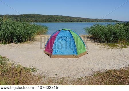 Tourist Tent For Trekking Eco Travel Or Fishing. Colourful Dome Tent On Lake Shore Or Camping Equipm