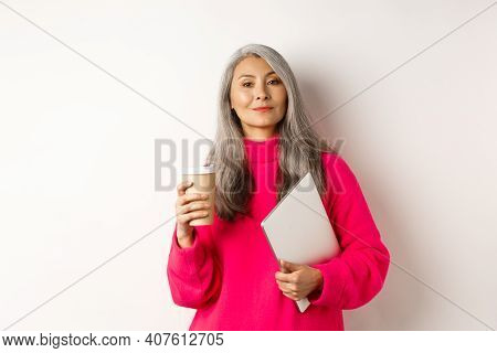 Stylish Asian Senior Businesswoman Drinking Coffee And Holding Laptop, Looking Confident And Smug At