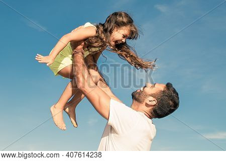 Happy Dad Holding Girl And Throwing Hands Up In Air. Handsome Father And Little Daughter Having Fun