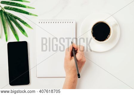 A Woman Writes, Makes Notes By Hand In An Empty Notebook, Over A Cup Of Coffee On The Phone On The D
