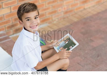 Portrait of smiling caucasian schoolboy using digital tablet on video call with male teacher. Online education staying at home in self isolation during quarantine lockdown.