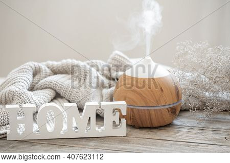 Aroma Composition With Modern Aroma Oil Diffuser On A Wooden Surface With A Knitted Element And A Wo