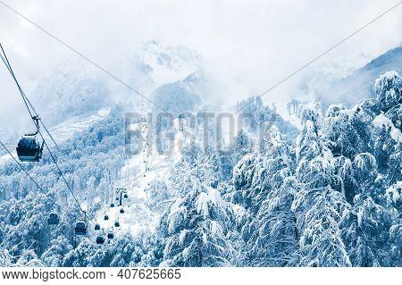 Gondola Lift In Ski Resort In Winter Mountains During Snowfall. Rosa Khutor, Sochi, Russia. Beautifu
