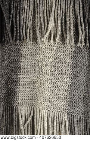 Close-up Of Fine-checked Woolen Texture In Gray. Winter Texture Concept, Fringe Scarf, Knitted Cloth
