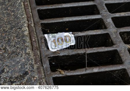 Money. American One Hundred Dollar Bill On The Grate Of The Storm Drain. Wet Banknote Snagged On A M
